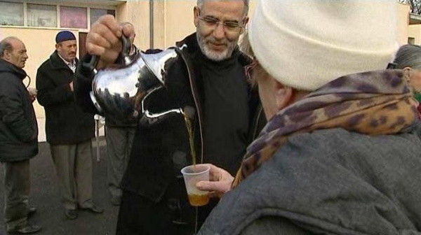 Une homme verse du thé à une femme devant la mosquée de Villeurbanne