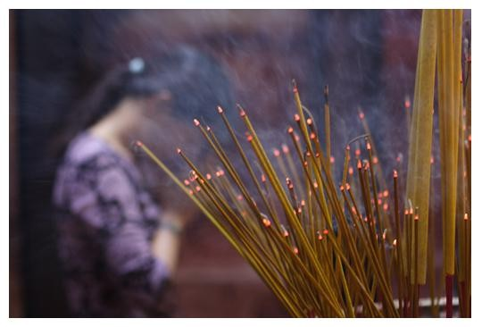 Une jeune femme prie dans la vapeur des bâtonnets d'encens